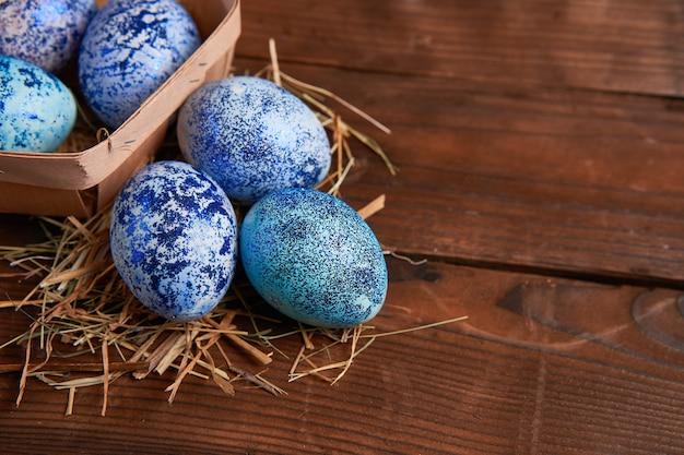 Ovos de galinha cosmos azul mentem em uma cesta de madeira redonda que fica sobre uma mesa de madeira escura.