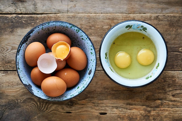Ovos de galinha crua em tigelas de metal em uma madeira