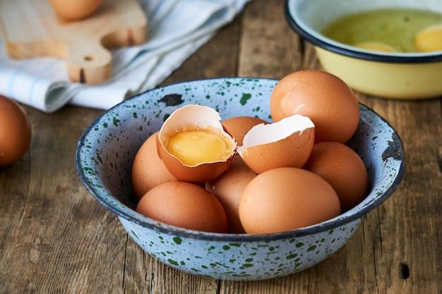 Ovos de galinha crua em uma tigela de metal em uma madeira