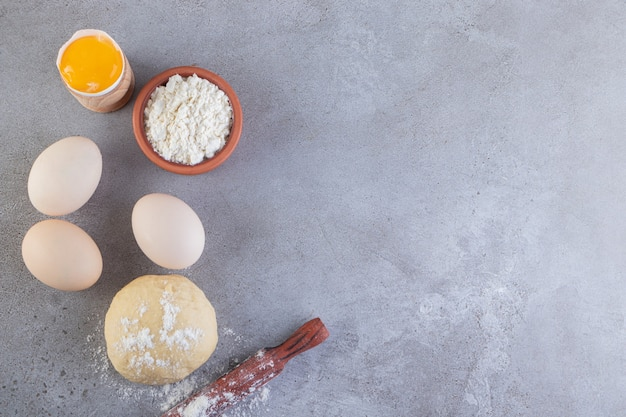 Ovos de galinha crus com massa e farinha colocados na mesa de pedra.