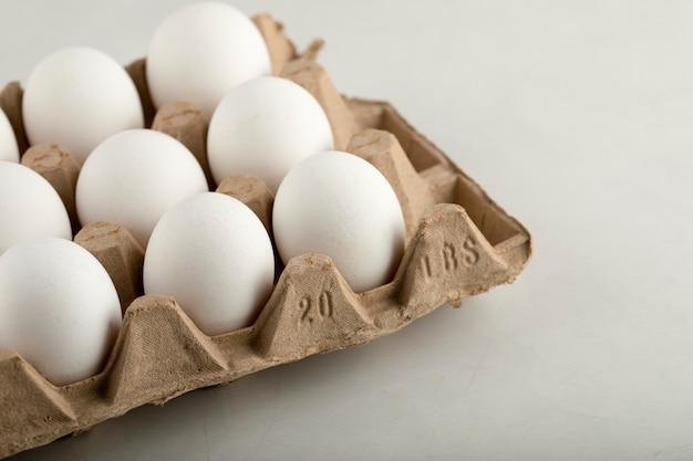 Ovos de galinha crus em caixa de ovo em uma superfície branca.