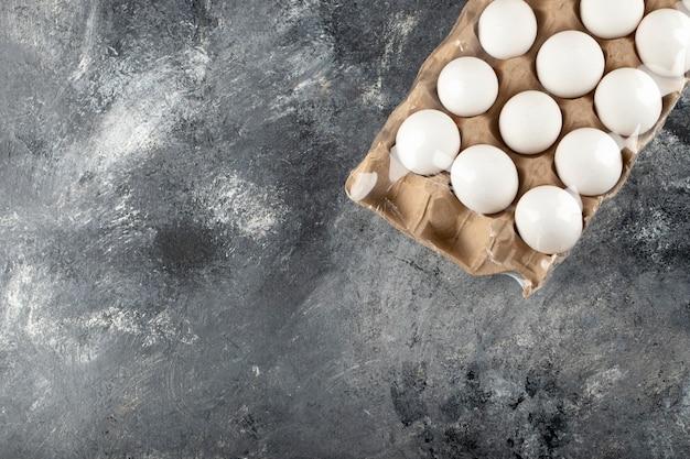 Ovos de galinha crus em caixa de ovo em uma superfície de mármore.