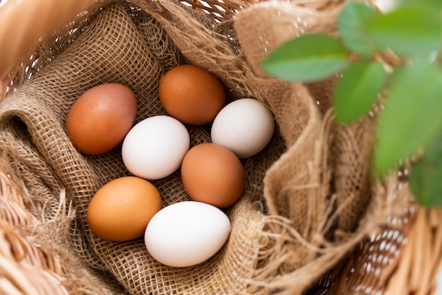 Ovos de galinha crus frescos na aldeia em uma cesta de vime rústica
