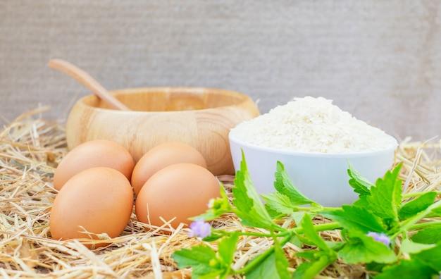 Ovos de galinha de boa qualidade com uma tigela de madeira, arroz cru e vegetais. fresco, adequado como um