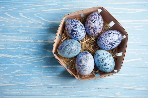 Ovos de galinha do cosmos azul mentem em uma cesta de madeira redonda que fica sobre uma mesa de madeira azul.