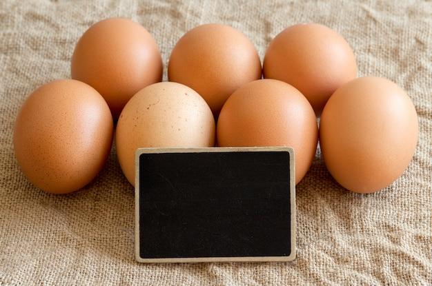 Ovos de galinha e lousa pequena close-up em uma serapilheira