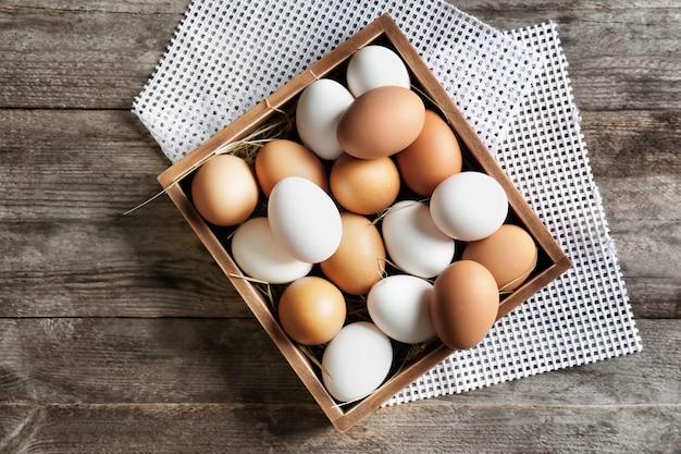 Ovos de galinha em caixa na mesa de madeira