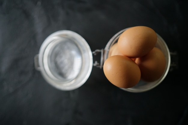 Ovos de galinha em frasco de vidro na ardósia com espaço de texto