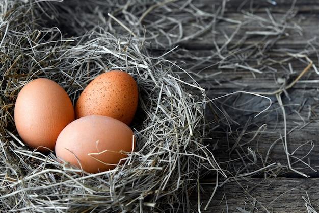 Ovos de galinha em ninhos de vime na vista superior do galinheiro. ovos orgânicos naturais no feno. ovos de galinha fresca.