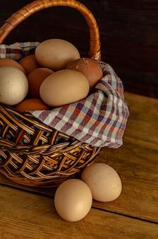 Ovos de galinha em um ninho feito de feno e cesta de vime