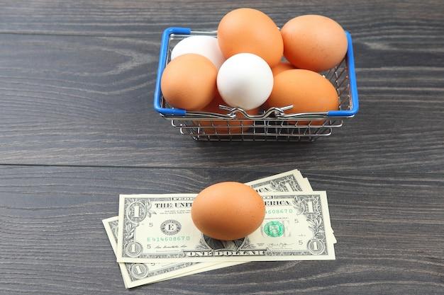 Ovos de galinha em uma cesta de supermercado contra um dólar em uma mesa de madeira. venda e negócios de produtos alimentícios
