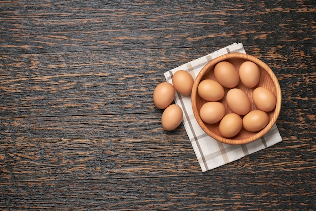 Ovos de galinha em uma tigela de madeira em uma mesa de cozinha, vista superior.