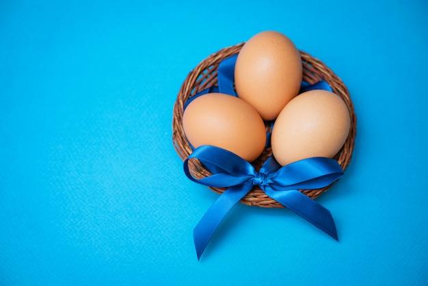 Ovos de galinha em uma tigela de palha com um laço azul sobre um fundo azul,