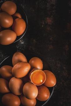 Ovos de galinha fazenda orgânica, em um prato, em uma superfície de metal enferrujada escura, cópia espaço vista superior