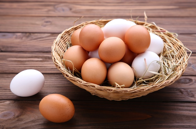 Ovos de galinha fresca na cesta no fundo marrom