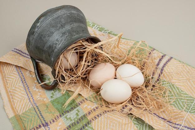 Ovos de galinha frescos com feno na xícara antiga na toalha de mesa.