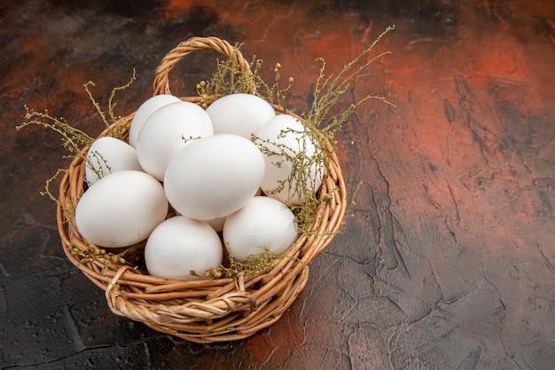 Ovos de galinha frescos de vista frontal dentro da cesta na superfície escura