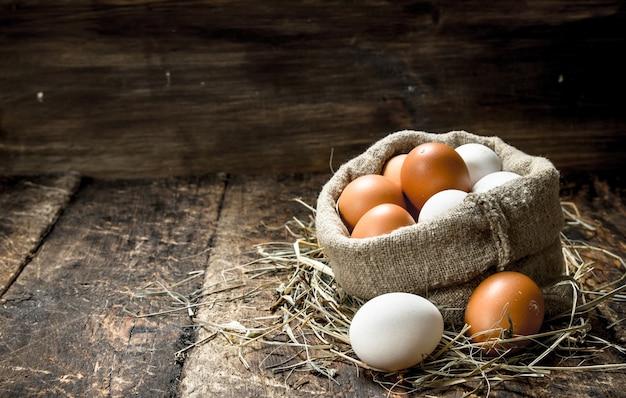 Ovos de galinha frescos em um saco velho em um fundo de madeira