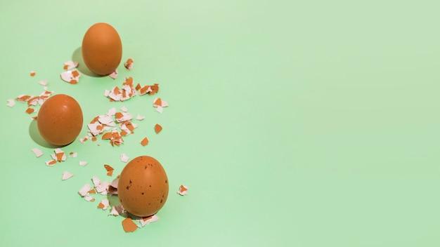 Ovos de galinha marrom com casca quebrada na mesa verde