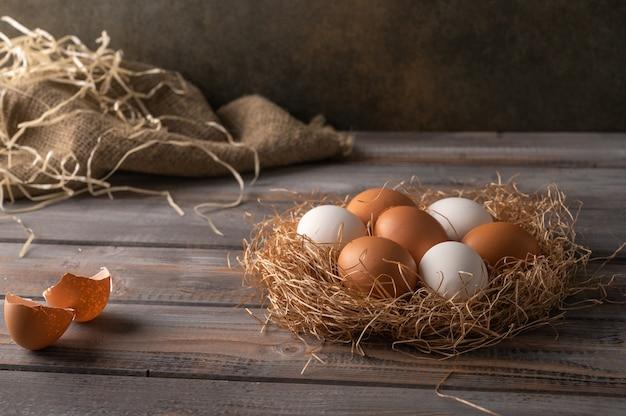 Ovos de galinha marrom e branca em um ninho de palha em fundo de madeira. estilo rústico. copie o espaço