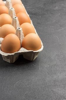 Ovos de galinha marrom em embalagem de papelão. copie o espaço. vista do topo