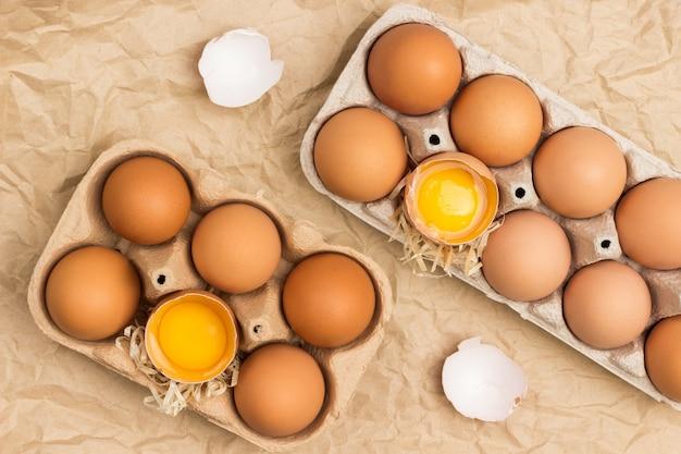 Ovos de galinha marrom em embalagem de papelão. ovo quebrado no recipiente. casca de ovo na mesa. postura plana