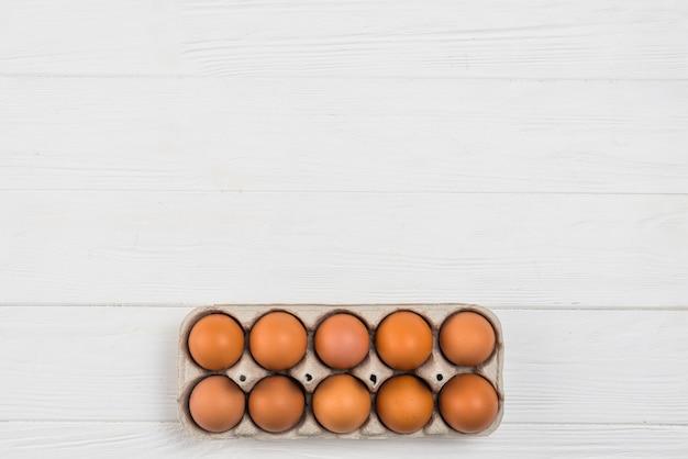 Ovos de galinha marrom em rack na mesa branca