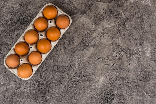 Ovos de galinha marrom em rack na mesa cinza
