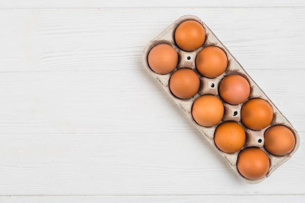 Ovos de galinha marrom em rack na mesa
