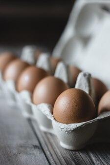 Ovos de galinha marrom em uma caixa na superfície de madeira.