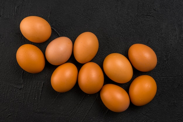 Ovos de galinha marrom espalhados na mesa preta