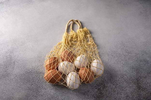 Ovos de galinha marrons e brancos em saco de barbante em um plano de fundo texturizado claro.