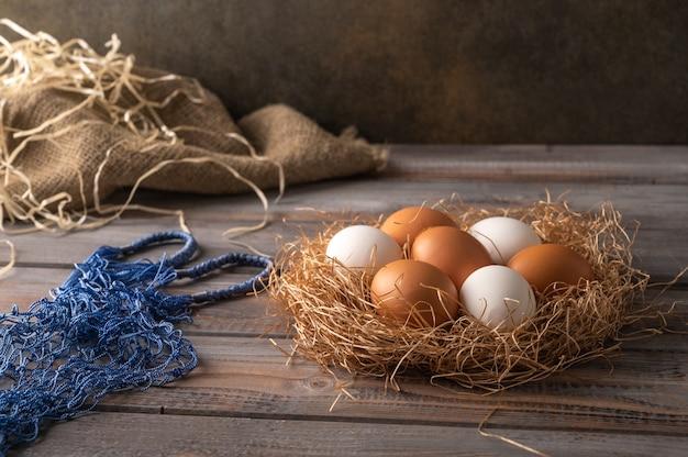 Ovos de galinha marrons e brancos em um ninho de palha em um fundo de madeira ao lado do saco de cordas ecológico estilo rústico copiar espaço
