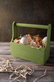 Ovos de galinha marrons e brancos em uma caixa de madeira com canudo. espaço sob seu texto.
