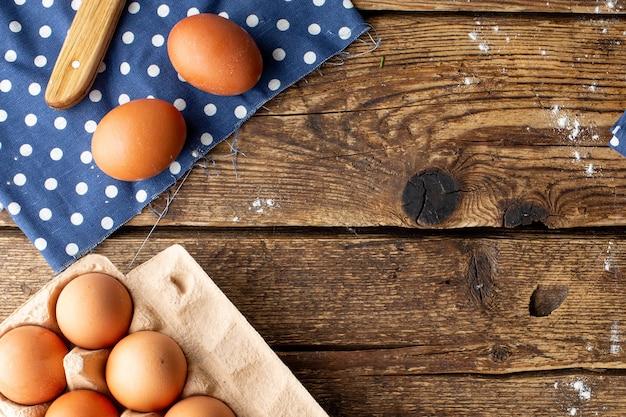 Ovos de galinha marrons embalados em um fundo de madeira