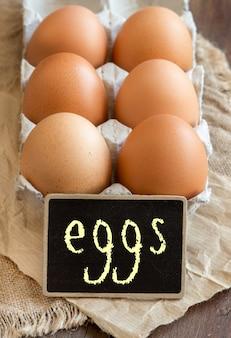 Ovos de galinha no pacote e pequena lousa close-up em uma mesa de madeira