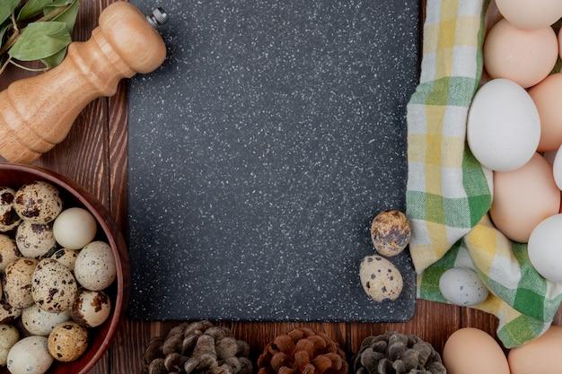Ovos de galinha vista superior em um balde de toalha de mesa com ovos de codorna em uma tigela de madeira sobre um fundo de madeira com espaço de cópia