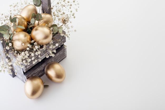 Ovos de ouro com flores da primavera, com espaço de cópia. o conceito de páscoa.