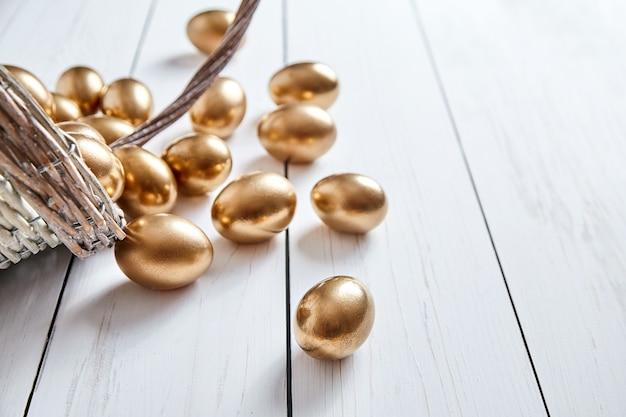 Ovos de ouro derramados de uma cesta de vime na mesa de madeira branca