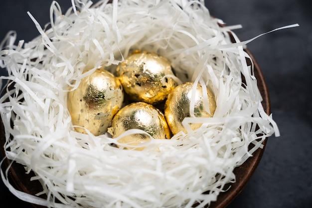 Ovos de ouro em um ninho no fundo escuro de madeira