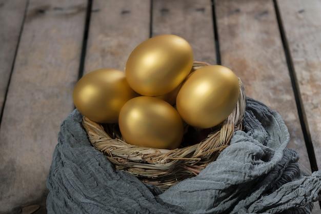 Ovos de ouro no ninho na mesa de madeira vintage escura