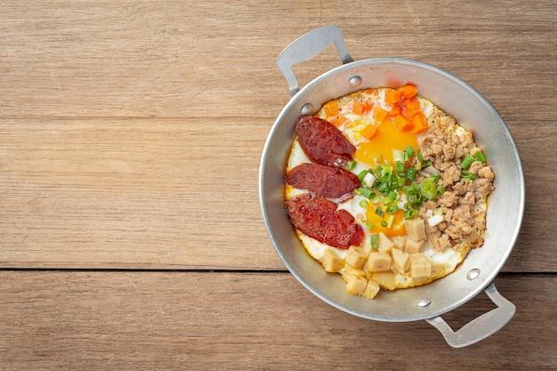 Ovos de panela polvilhados com salsicha chinesa, bacon em cubos, café da manhã.