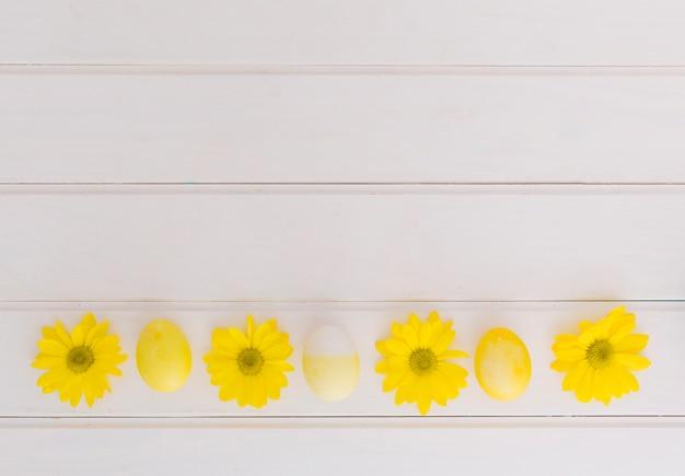 Ovos de páscoa amarelos e flores na mesa