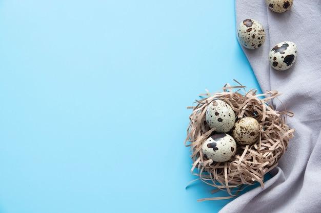 Ovos de páscoa azuis e buquê de flores na mesa rústica de madeira