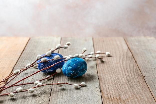 Ovos de páscoa azuis e galhos de salgueiro na mesa de madeira