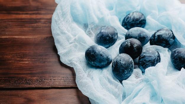 Ovos de páscoa azuis no tecido no fundo de tábuas de madeira