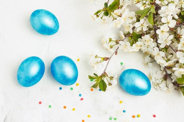 Ovos de páscoa azuis roxos, flores de primavera maçã, cereja, doces coloridos em um fundo de pedra branco