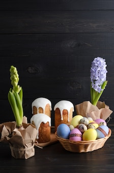 Ovos de páscoa, bolo de páscoa e jacintos sobre um fundo escuro