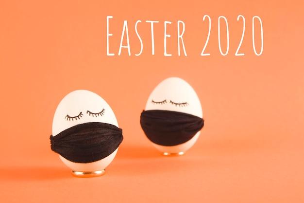 Ovos de páscoa brancos com olhos em máscaras médicas pretas proteção contra covid-19.