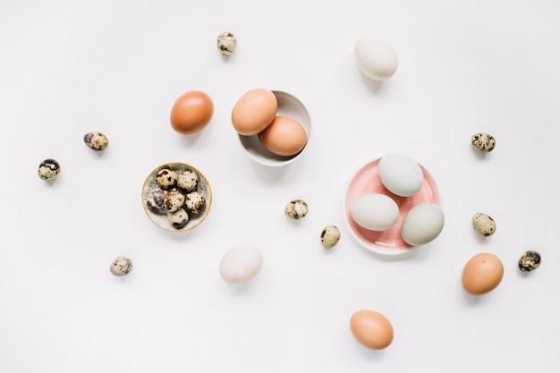 Ovos de páscoa brancos e marrons e ovos de codorna na superfície branca